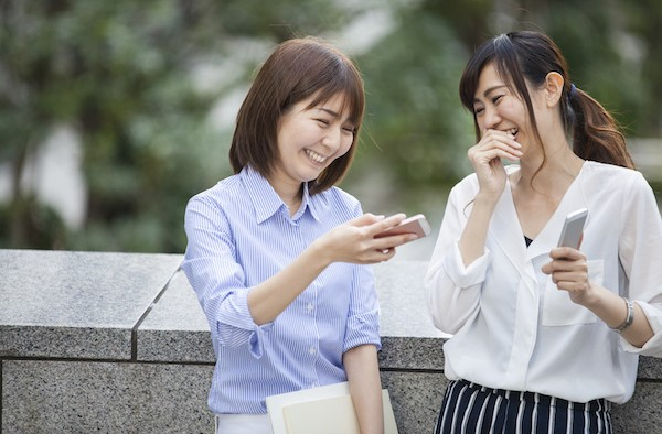 Two business women are talking while watching smartphone