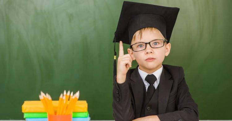 Surprised boy in graduation cap raised his finger.